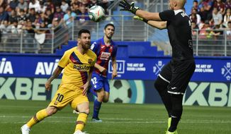 Barcelona's Lionel Messi, left, tries to beat Eibar's goalkeeper Marko Dmitrovic during a Spanish La Liga soccer match between Eibar and FC Barcelona at the Ipurua stadium in Eibar, Spain, Saturday Oct. 19, 2019. (AP Photo/Alvaro Barrientos)