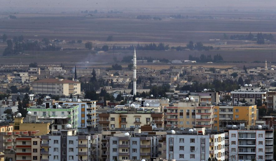 In this photo taken from the Turkish side of the border between Turkey and Syria, in Ceylanpinar, Sanliurfa province, southeastern Turkey, a new of Ras al-Ayn, Syria, Friday, Oct. 18, 2019. Fighting broke out in the morning hours in the Syrian border town which has been a flashpoint in the fight between Turkey and Kurdish forces despite a U.S.-brokered cease-fire that went into effect overnight. The fighting died down in mid-morning. (AP Photo/Lefteris Pitarakis)