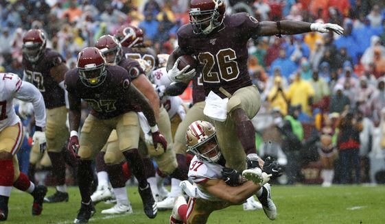 Washington Redskins running back Adrian Peterson (26) rushes against San Francisco 49ers defensive end Nick Bosa (97) in the first half of an NFL football game, Sunday, Oct. 20, 2019, in Landover, Md. (AP Photo/Alex Brandon)