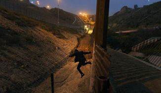 In this Dec. 21, 2018, file photo, a Honduran youth jumps from the U.S. border fence in Tijuana, Mexico. (AP Photo/Daniel Ochoa de Olza, File)