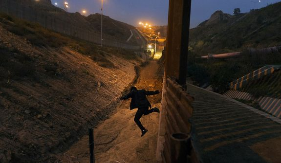 FILE - In this Dec. 21, 2018, file photo, a Honduran youth jumps from the U.S. border fence in Tijuana, Mexico.   California's attorney general filed a lawsuit Monday, Feb. 18, 2019, against President Donald Trump's emergency declaration to fund a wall on the U.S.-Mexico border. Xavier Becerra released a statement Monday saying 16 states  including California  allege the Trump administration's action violates the Constitution. (AP Photo/Daniel Ochoa de Olza, File)