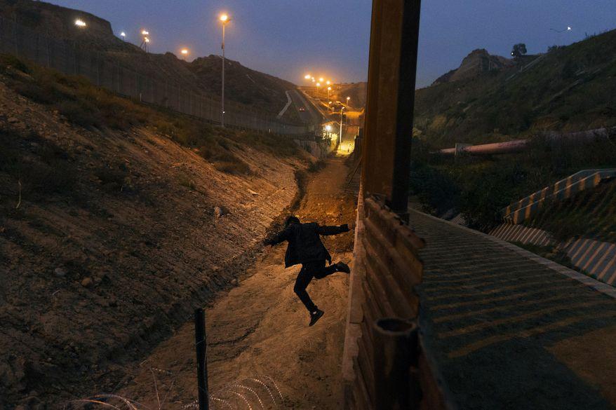 In this Dec. 21, 2018, file photo, a Honduran youth jumps from the U.S. border fence in Tijuana, Mexico. (AP Photo/Daniel Ochoa de Olza, File)