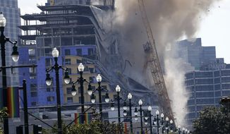 Two large cranes from the Hard Rock Hotel construction collapse come crashing down after being detonated for implosion in New Orleans, Sunday, Oct. 20, 2019. New Orleans officials set off several explosions Sunday intended to topple two cranes that had been looming over the ruins of a partially collapsed hotel. (AP Photo/Gerald Herbert)
