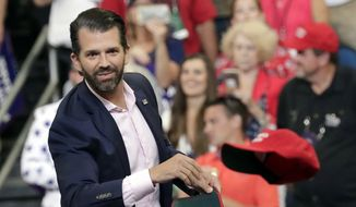 Donald Trump Jr. throws hats to supporters at a campaign rally for President Donald Trump in Orlando, Fla. (AP Photo/John Raoux)