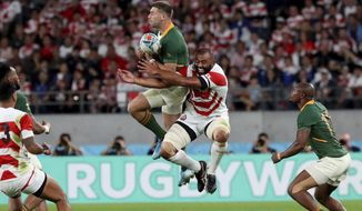 South Africa's Handre Pollard, center left, and Japan's Michael Leitch vie for the ball during the Rugby World Cup quarterfinal match at Tokyo Stadium in Tokyo, Japan, Sunday, Oct. 20, 2019. (AP Photo/Eugene Hoshiko)