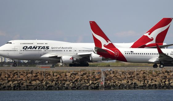 FILE - In this Aug. 20, 2015 file photo, two Qantas planes taxi on the runway at Sydney Airport in Sydney, Australia. Australia's Qantas has completed the first non-stop commercial flight from New York to Sydney Sunday, Oct. 20, 2019, which was used to run a series of tests to assess the effects of ultra-long-haul flights on crew fatigue and passenger jetlag. (AP Photo/Rick Rycroft)