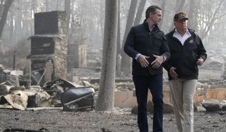 In this Nov. 17, 2018, file photo, President Donald Trump talks with California Gov.-elect Gavin Newsom during a visit to a neighborhood destroyed by the wildfires in Paradise, Calif. California has long used its status as the nation's most populous state (nearly 40 million people) and the world's fifth-largest economy (about $3 trillion) to pass trend-setting policies. But that role has crystallized in the Trump era, with California Democrats positioning the state as the nation's defense system against rollbacks of environmental and health care laws and the federal crackdown on illegal immigration, among other issues. First-year Gov. Gavin Newsom relishes his role as a Trump adversary and the leader of a state that does things before others. (AP Photo/Evan Vucci, File)