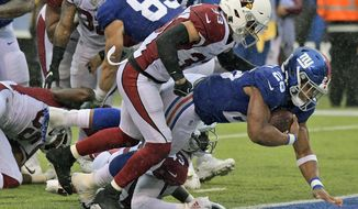 New York Giants' Saquon Barkley, right, scores a touchdown during the second half of an NFL football game against the Arizona Cardinals, Sunday, Oct. 20, 2019, in East Rutherford, N.J. (AP Photo/Bill Kostroun)