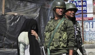 A Kashmiri woman walks past paramilitary soldiers standing guard near the site of a gunbattle in Bijbehara, south of Srinagar, Indian controlled Kashmir, Wednesday, Oct. 16, 2019. Indian police officer Parvaiz Ahmed said Indian security forces killed three militants in an exchange of gunfire in southern Kashmir, following intelligence that a group of militants was hiding in Bijbehara town. Indian-administered Kashmir has experienced unrest and sporadic anti-government protests since New Delhi revoked its special status. (AP Photo/Mukhtar Khan)
