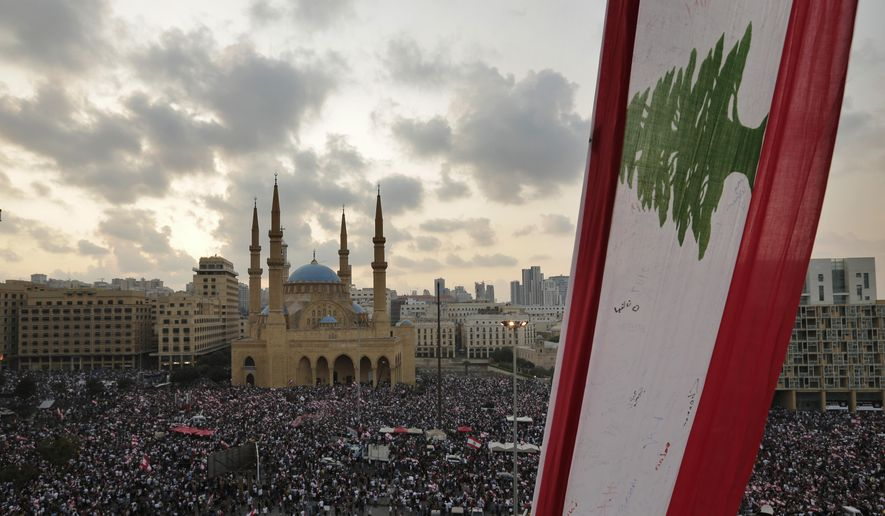 Anti-government protesters shout slogans in Beirut, Lebanon, Sunday, Oct. 20, 2019. Tens of thousands of Lebanese protesters of all ages gathered Sunday in major cities and towns nationwide, with each hour bringing hundreds more people to the streets for the largest anti-government protests yet in four days of demonstrations. (AP Photo/Hassan Ammar)