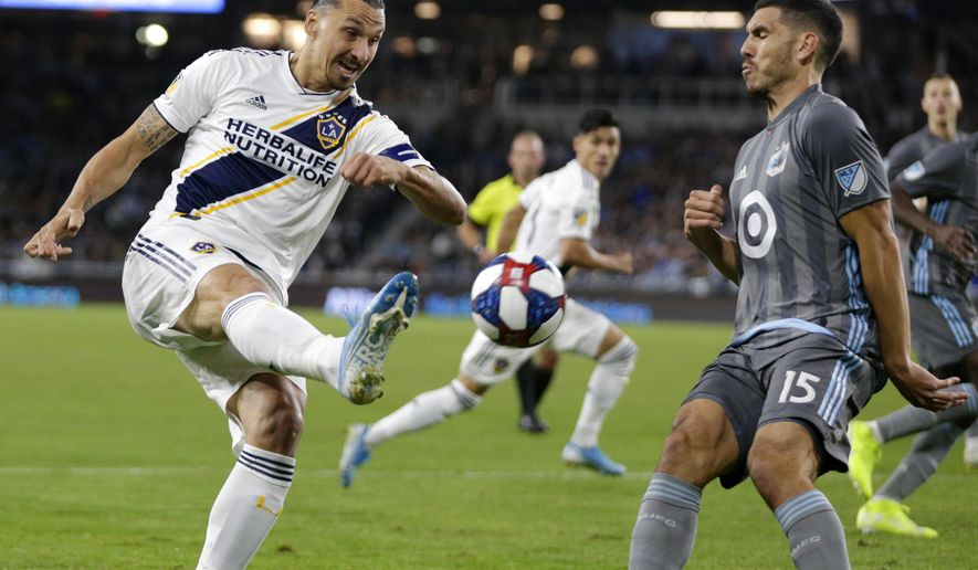 Los Angeles Galaxy Mid fielder Zlatan Ibrahimovic, left, shoots in front of Minnesota United defender Michael Boxall (15) during the first half of an MLS first-round playoff match Sunday, Oct. 20, 2019, in St. Paul, Minn.(AP Photo/Andy Clayton-King)