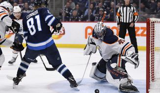 Edmonton Oilers' Mike Smith (41) makes a save against Winnipeg Jets' Kyle Connor (81) during second-period NHL hockey game action in Winnipeg, Manitoba, Sunday, Oct. 20, 2019. (Fred Greenslade/The Canadian Press via AP)