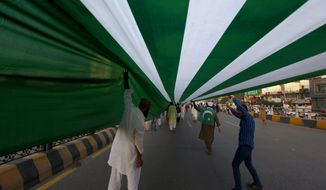 People carry a five kilometer, or about three mile, long representation of a Kashmiri flag during a rally to express solidarity with Indian Kashmiris, in Islamabad, Pakistan, Sunday, Oct. 20, 2019. Tensions between Pakistan and India, two nuclear-armed countries, has increased since Aug. 5, when India downgraded the autonomy of its side of Kashmir and imposed tighter controls on the area. (AP Photo/Anjum Naveed)