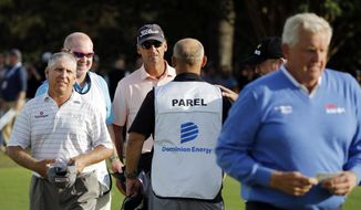 Co-leaders Scott Parel, left, and Tommy Toles, wearing cap, walk off the final hole at 12 under par, one stroke ahead of Colin Montgomerie, right, after the second round of the Dominion Energy Charity Classic golf tournament in Richmond, Va., Saturday, Oct. 19, 2019. Montgomerie missed a tying birdie attempt after engaging noisy fans in the stands. (Joe Mahoney/Richmond Times-Dispatch via AP)