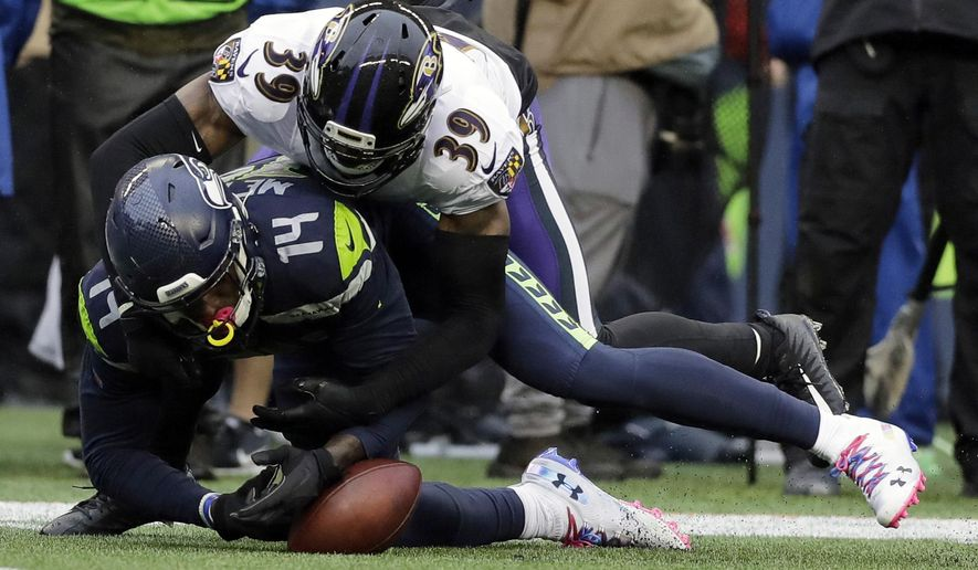 Seattle Seahawks wide receiver D.K. Metcalf (14) fumbles as he is hit by Baltimore Ravens cornerback Brandon Carr (39) during the second half of an NFL football game, Sunday, Oct. 20, 2019, in Seattle. Ravens' Marlon Humphrey recovered the fumble and ran for a touchdown. (AP Photo/John Froschauer)