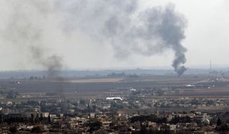 In this photo taken from the Turkish side of the border between Turkey and Syria, in Ceylanpinar, Sanliurfa province, southeastern Turkey, smoke billows from fires in Ras al-Ayn, Syria, Sunday, Oct. 20, 2019. Turkey's defense ministry says one soldier has been killed amid sporadic clashes with Kurdish fighters in northern Syria, despite a U.S.-brokered cease-fire. The ministry also said it allowed a 39-vehicle humanitarian convoy to enter Ras al-Ayn, a key border town that's seen some of the heaviest fighting. (AP Photo/Lefteris Pitarakis)