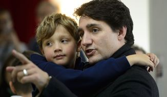 Canadian Prime Minister Liberal Leader Justin Trudeau holds his son Hadrien as he waits to vote in Montreal, Monday, Oct. 21, 2019. (Paul Chiasson/The Canadian Press via AP)