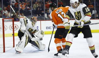 Philadelphia Flyers' Michael Raffl (12) scores against Vegas Golden Knights' Oscar Dansk, left, as Knights' Jon Merrill (15) watches during the second period of an NHL hockey game Monday, Oct. 21, 2019, in Philadelphia. (AP Photo/Matt Rourke)