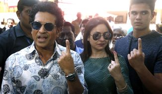 Former Indian cricketer Sachin Tendulkar, left, with his wife Anjali and son Arjun pose for media after casting their votes in Mumbai, India, Monday, Oct. 21, 2019. Voting is underway in two Indian states of Maharashtra in the west and Haryana in the north where the Hindu nationalist Bharatiya Janata Party (BJP) headed by prime minister Narendra Modi is trying to win a second consecutive term. (AP Photo/Rafiq Maqbool)