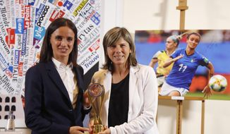 The coach of the Italian women national soccer team, Milena Bertolini, and forward Barbara Bonansea, left, pose with the Invictus sports award, at the Foreign Press Association in Rome, Monday, Oct. 21, 2019. The Italy women's team was awarded Monday with the Foreign Press Association's Invictus sports award for raising the profile of the women's game by reaching the World Cup quarterfinals. (AP Photo/Andrew Medichini)
