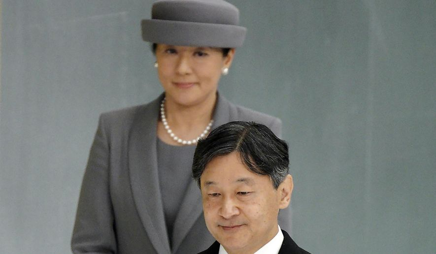 FILE - In this Aug. 15, 2019, file photo, Japanese Emperor Naruhito, accompanied by Empress Masako, walks to deliver his remarks during a memorial ceremony for the war dead at Nippon Budokan Martial Arts Hall in Tokyo. (AP Photo/Eugene Hoshiko, File)