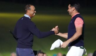 Tiger Woods of the United States, left, and Jason Day of Australia, right, hold their hands on the 18th hole after the Challenge: Japan Skins event ahead of the Zozo Championship PGA Tour at Accordia Golf Narashino C.C. in Inzai, east of Tokyo, Monday, Oct. 21, 2019. (AP Photo/Lee Jin-man)