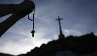 In this Thursday, Oct. 3, 2019 photo, a worshiper holds a rosary at the Valley of the Fallen mausoleum near El Escorial, outskirts of Madrid, Spain. After a tortuous judicial and public relations battle, Spain's Socialist government has announced that Gen. Francisco Franco's embalmed body will be relocated from a controversial shrine to a small public cemetery where the former dictator's remains will lie along his deceased wife. (AP Photo/Alfonso Ruiz)