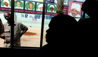 FILE - In this April 10, 2010 file photo, Sudanese women looks through a bus window as it passes posters supporting then Sudanese President and presidential candidate Omar al-Bashir, right, and his ruling National Congress Party candidates, in Khartoum, Sudan. Activists are calling for mass protests in the capital, Khartoum, and elsewhere across the country to demand the disbanding of the National Congress Party. The Sudanese Professionals' Association, which spearheaded the uprising against Bashir's rule, said the protests Monday, Oct. 21, 2019, will also renew demands to step up an independent investigation into the deadly break-up of protests in June. (AP Photo/Amr Nabil, File)
