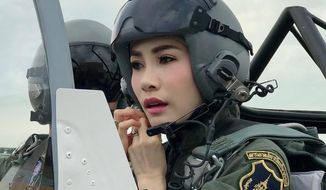 This undated photo posted Monday, Aug. 26, 2019, on the Thailand Royal Office website shows Major General Sineenatra Wongvajirabhakdi, the royal noble consort of King Maha Vajiralongkorn, in an aircraft cockpit.  Late Monday, Oct. 21, 2019, it was announced that Sineenatra was stripped his royal noble consort of her titles and military ranks for disloyalty, accusing her of seeking to undermine the position of his official wife for her own benefit. (Thailand Royal Office via AP)