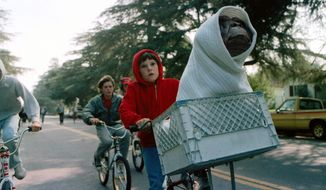 """This image released by Universal Pictures shows Henry Thomas as Elliott and E.T. in a basket on a bicycle in a scene from director Steven Spielberg's 1982 movie """"E.T.: The Extra-Terrestrial."""" As astronomers debate whether it would be a good idea to send signals into the universe to look for extra-terrestrial life, in science-fiction movies, aliens sometimes come in peace — and often do not. (AP Photo/Universal Pictures)"""