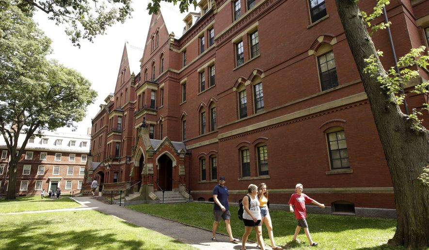 In this Tuesday, July 16, 2019 photo people walk along a sidewalk on the campus of Harvard University, in Cambridge, Mass. (AP Photo/Steven Senne)
