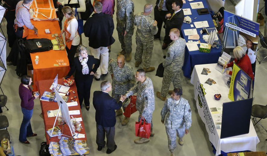 """Attendees talk with recruiters, Thursday, Oct. 23, 2014, at a job fair that was part of a """"transition summit"""" intended to provide employment and educational information to soldiers who may exit military service in the next year, at Joint Base Lewis-McChord, Wash. More than 4,500 service members attended the three-day event. (AP Photo/Ted S. Warren)"""