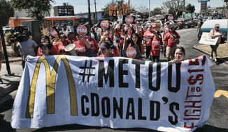 FILE - In this Sept. 18, 2018, file photo, McDonald's workers carry a banner and march towards a McDonalds in south Los Angeles. Roughly a third of American workers say they've changed how they act at work in the past year, as the #MeToo movement has focused the nation's attention on sexual misconduct. That's according to a new poll of full- or part-time workers released Tuesday by The Associated Press-NORC Center for Public Affairs Research and the software company SAP.  (AP Photo/Richard Vogel, File)