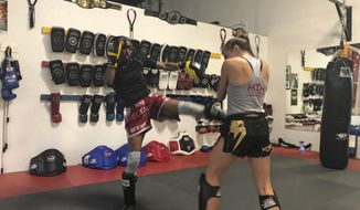 """In this photo taken Oct. 11, 2019, California women's basketball coach Charmin Smith spars with Alexa Terry during a Muay Thai boxing class in Oakland, Calif. """"It's definitely my passion outside of basketball. I've found a whole new community. I have new teammates, new family with our Muay Thai-minded family and Coach Jay,"""" Smith says. """"And it's been truly phenomenal and I've learned another level of discipline and commitment. The technique and the skill that it takes to learn the art of Muay Thai has definitely made me a better basketball coach."""" (AP Photo/Janie McCauley)"""