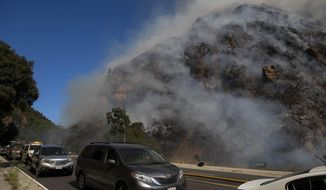 Palisades residents flee the area as a wildfire erupts in the Pacific Palisades area of Los Angeles, Monday, Oct. 21, 2019. (AP Photo/Christian Monterrosa)