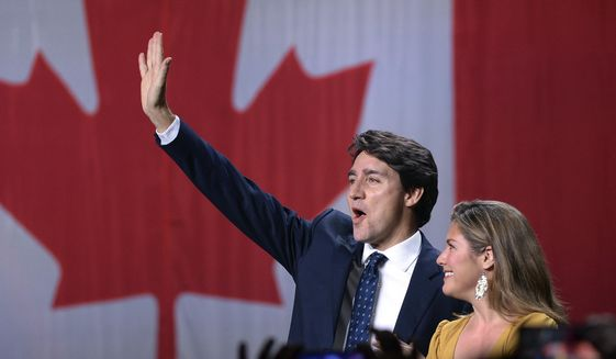 Liberal leader Justin Trudeau and wife Sophie Gregoire Trudeau wave as they go on stage at Liberal election headquarters in Montreal, Monday, Oct. 21, 2019. (Ryan Remiorz/The Canadian Press via AP)