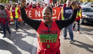 Chicago Teachers Union members and their supporters march through the Near West Side after a rally in Union Park on day five of a Chicago Public Schools district-wide strike, Monday, Oct. 21, 2019. Chicago Public Schools announced Sunday night that classes and after school activities are canceled Monday as the strike enters its first full week. The work stoppage began on Thursday. (Ashlee Rezin Garcia/Chicago Sun-Times via AP) **FILE**