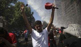An anti-government protester raises his hands during clashes with police in Santiago, Chile, Tuesday, Oct. 22, 2019. The government said Tuesday that 15 people have died in five days of rioting, arson and violent clashes that were sparked by a hike in subway fares and have almost paralyzed the country. (AP Photo/Rodrigo Abd)
