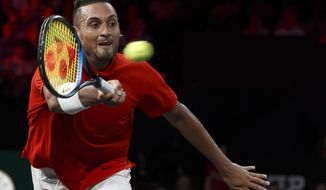 """FILE - In this Sept. 21, 2019 file photo, Nick Kyrgios returns a ball to Roger Federer during their singles match at the Laver Cup tennis event, in Geneva, Switzerland. Australia captain Lleyton Hewitt says he has been willing to overlook Kyrgios' recent outbursts on the ATP Tour to select the talented but wayward star in his team for the revamped Davis Cup finals. Kyrgios is currently serving six months probation on the ATP tour after a meltdown at the Cincinnati tournament in August and calling the ATP """"pretty corrupt"""" during this year's US Open. (Salvatore Di Nolfi/Keystone via AP, File)"""
