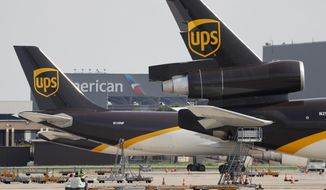 In this June 24, 2019, photo workers prepare to unload a UPS aircraft after it arrived at Dallas-Fort Worth International Airport in Grapevine, Texas. United Parcel Service Inc. reports financial earns on Tuesday, Oct. 22, 2019. (AP Photo/Tony Gutierrez)
