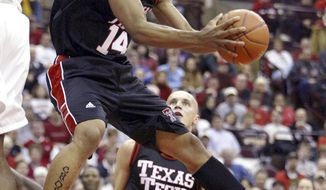 FILE - In this Jan 4, 2004, file photo, Texas Tech's Andre Emmett (14) tries to shoot around Ohio State's Terence Dials during the first half of an NCAA basketball game at Value City Arena in Columbus, Ohio. WFAA-TV reports investigators say Keith Johnson and a second suspect allegedly shot former NBA and Texas Tech standout Emmett during a Sept. 23, 2019, robbery attempt. (AP Photo/Ron Schwane, File)