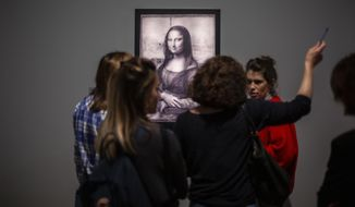 Journalists gather near a Mona Lisa image by Leonardo da Vinci during a visit at the Louvre museum Sunday, Oct. 20, 2019 in Paris. A unique group of artworks is displayed at the Louvre museum in addition to its collection of paintings and drawings by the Italian master. The exhibition opens to the public on Oct.24, 2019. (AP Photo/Rafael Yaghobzadeh)
