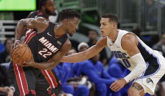 Miami Heat's Jimmy Butler (22) looks to get past Orlando Magic's Aaron Gordon, right, during the second half of an NBA preseason basketball game, Thursday, Oct. 17, 2019, in Orlando, Fla. (AP Photo/John Raoux)