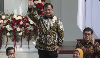 Newly appointed Defense Minister Prabowo Subianto who is the former rival of Indonesian President Joko Widodo in last April's election, waves as he is introduced during the announcement of the new cabinet at Merdeka Palace in Jakarta, Indonesia, Wednesday, Oct. 23, 2019. (AP Photo/Dita Alangkara)