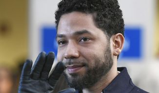 Actor Jussie Smollett smiles and waves to supporters before leaving Cook County Court after his charges were dropped in Chicago, March 26, 2019. A decision is expected on a motion in federal court Tuesday, Oct. 22 by Smollertt's lawyer asking that the city of Chicago's lawsuit against him requesting costs of investigation be dismissed.(AP Photo/Paul Beaty) ** FILE **