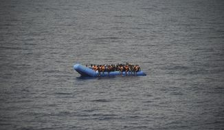 FILE - In this Sept. 17, 2019, file photo, migrants aboard a blue plastic boat are seen in the Mediterranean Sea. The U.N. refugee agency is investigating why Malta last week allegedly asked the Libyan coast guard to intercept a migrant boat in a zone of the Mediterranean under Maltese responsibility, in possible violation of maritime law, a U.N. official said Tuesday, Oct. 22, 2019. (AP Photo/Renata Brito)