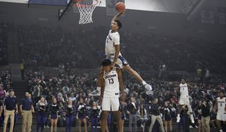 Connecticut's James Bouknight, top, leaps over teammate Richard Springs to dunk the ball during UConn's men's and women's basketball teams' annual First Night celebration in Storrs, Conn. (AP Photo/Jessica Hill)