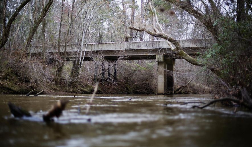 This Feb. 22, 2018, file photo shows a bridge that spans the Apalachee River at Moore's Ford Road where in 1946 two young black couples were stopped by a white mob who dragged them to the riverbank and shot them multiple times in Monroe, Ga. The gruesome lynching is prompting a U.S. court to consider whether federal judges can order grand jury records unsealed in old cases with historical significance. (AP Photo/David Goldman, File) **FILE**