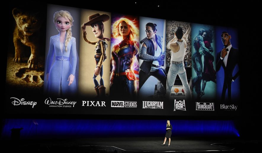 In this April 3, 2019, file photo characters from Disney and Fox movies are displayed behind Cathleen Taff, president of distribution, franchise management, business and audience insight for Walt Disney Studios during the Walt Disney Studios Motion Pictures presentation at CinemaCon 2019, the official convention of the National Association of Theatre Owners (NATO) at Caesars Palace in Las Vegas. (Photo by Chris Pizzello/Invision/AP, File) ** FILE **
