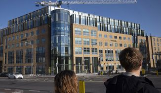 In this Oct. 6, 2019, photo people walk by WeWork offices in Dublin, Ireland. The Wall Street Journal is reporting on Tuesday, Oct. 22, that WeWork is being taken over by the Japanese investment bank that invested billions in the company before its botched effort to go public. (AP Photo/Mark Lennihan)